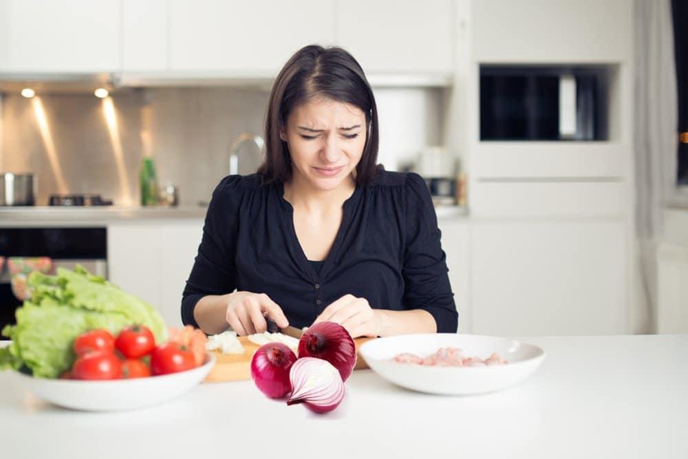 Девушка режет луковицу